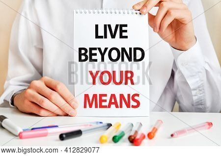 A Sheet Of Paper With Text Live Beyond Your Means, Multicolored Markers On A White Table. Business A