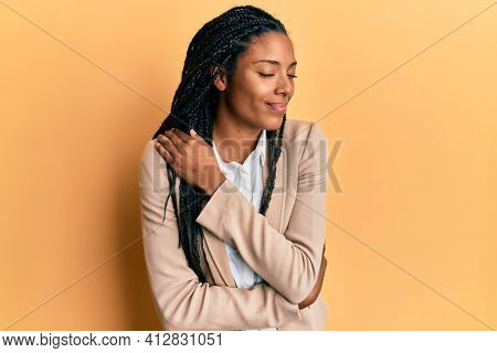African american woman wearing business jacket hugging oneself happy and positive, smiling confident. self love and self care
