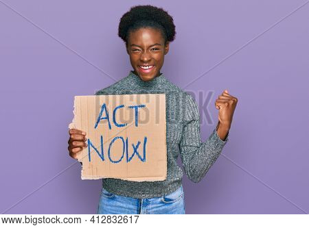 Young african american girl holding act now banner screaming proud, celebrating victory and success very excited with raised arms