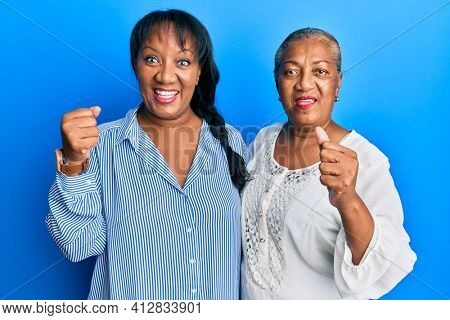 Hispanic family of mother and daughter hugging together with love screaming proud, celebrating victory and success very excited with raised arms