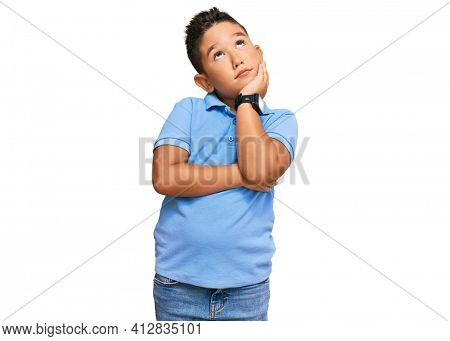Little boy hispanic kid wearing casual clothes with hand on chin thinking about question, pensive expression. smiling and thoughtful face. doubt concept.
