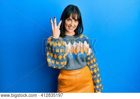 Young hispanic woman wearing casual winter sweater showing and pointing up with fingers number three while smiling confident and happy.