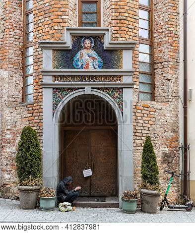 Vilnius, Lithuania - March 14, 2021: Beggar Sits In Front Of The Entrance Of The Sanctuary Of The Di