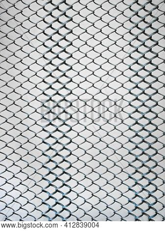 Metal Springy Mesh With Chain Link On A Beige Background, Part Of An Old Steel Mattress With Iron Li