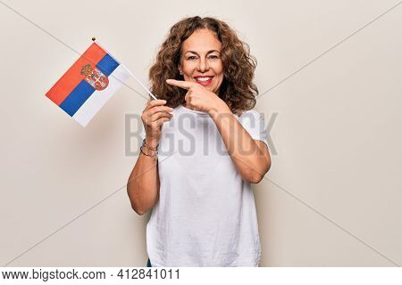 Middle age beautiful patriotic woman holding serbian flag over isolated white background smiling happy pointing with hand and finger