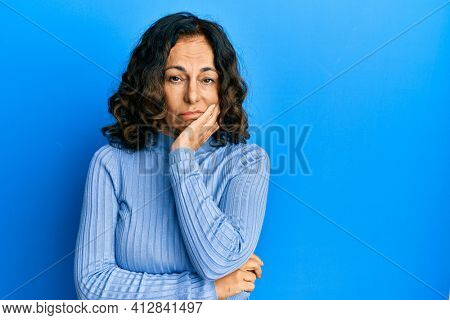 Middle age hispanic woman wearing casual clothes thinking looking tired and bored with depression problems with crossed arms.