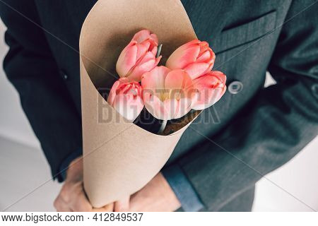 Elegant Man Holding Bouquet Of Pink Tulips Wrapped In Craft Paper.surprise For Your Beloved Woman.ro