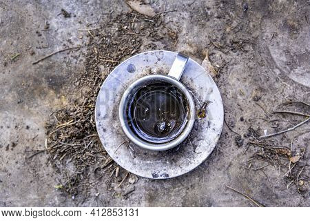 Old Decaying Metal Cup And Saucer With Dirty Coffee Leftovers On The Ground