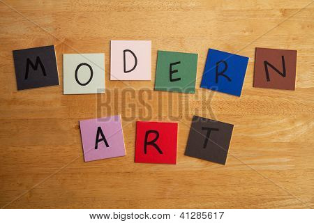 'MODERN ART' in words and letters on color tiles and wooden background, sign or poster for the arts, painting, education, post modernism etc. poster