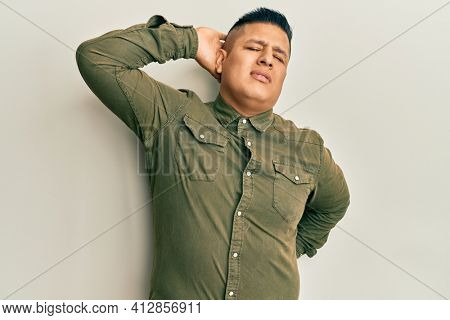 Young latin man wearing casual clothes suffering of neck ache injury, touching neck with hand, muscular pain