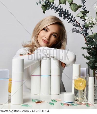 Healthy Wealthy Blonde Woman In White Stylish Pullover Sits At Table Leaning On Set Of Jars And Tube