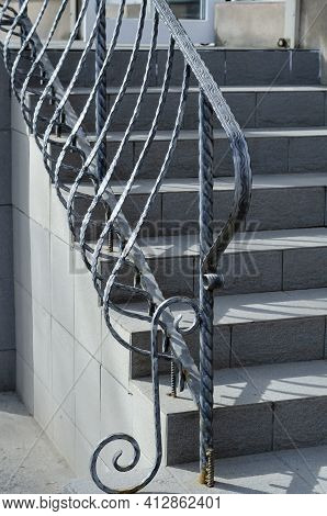 Gray Stone Staircase With Wrought Iron Railings. Graceful Railings Enclose The Steps Covered With Ce