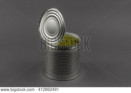 Open Tin Can On A Gray Background. Canned Green Peas. The Can Was Opened With A Knife. Ready-to-eat