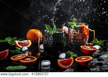 Blood Orange Moscow Mule Alcohol Cocktails With Fresh Mint Leaves And Ice In Copper Mugs, Splashes A