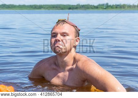 A Teenager With A Water Lily Leaf On His Head Frolics In The Water On A Hot Sunny Summer Day And Is
