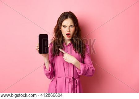 Technology Concept. Angry Girl Points At Her Smartphone Screen And Staring Judgemental At Camera, De