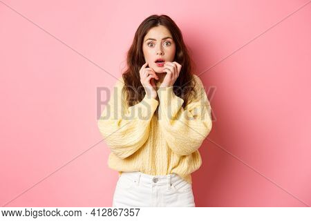 Portrait Of Scared And Shocked Brunette Girl, Gasping And Holding Hands Near Lips, Staring Frightene