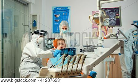 Pediatric Dentist Wearing Protection Suit Treating Girl Patient In New Normal Stomatological Unit Sh