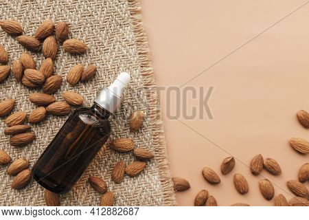 Almond Essential Oil In Glass Bottle, Raw Almond Kernels. Cosmetic Concept On Beige Background With