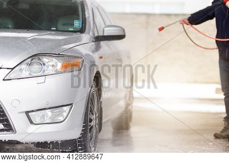 Person Washing Car With Water And Soap In Carwash.