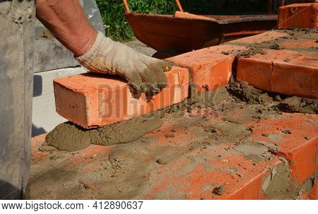 A Mason Person Is Laying A Brick Wall Or Foundation Of A New House. A Close-up Of A Brickwork When A