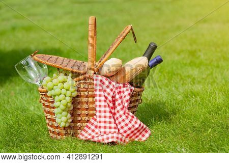 Picnic basket with wine, baguette and grapes on garden sunny grass