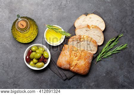 Ripe olives, olive oil and ciabatta bread. Top view flat lay