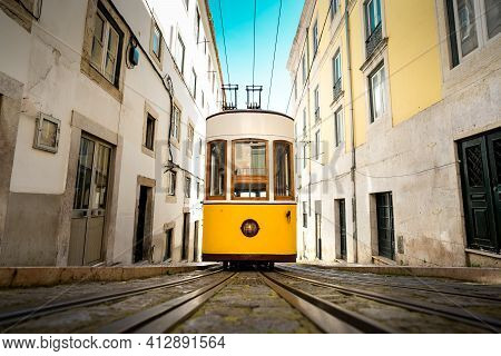 Trams In Lisbon. Famous Retro Yellow Funicular Tram On Narrow Streets Of Lisbon. Tourist Sightseeing