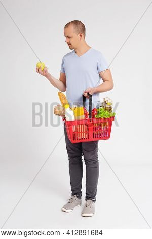 Full Length Portrait Of Young Man With Shopping Basket Full Of Products Choosing Fruits Over White