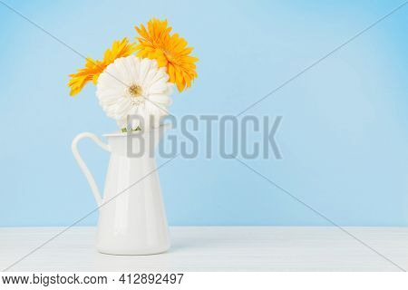 Colorful gerbera flowers over blue background. Top view flat lay with copy space