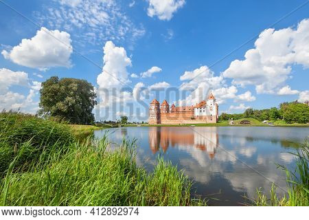 Summer Landscape With Mir Castle Reflecting In The Water Of A Pond, Belarus