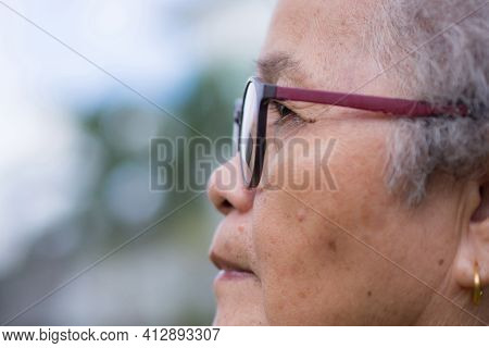 Side View Of A Senior Woman Wearing Glasses And Looking Away While Standing In A Garden. Space For T