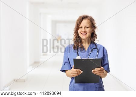 Young female intern in a blue uniform holding a clipboard in a hospital corridor