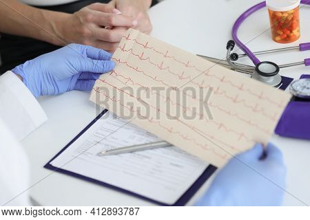 Doctor Holds Transcript Of Patient Cardiogram In His Hands
