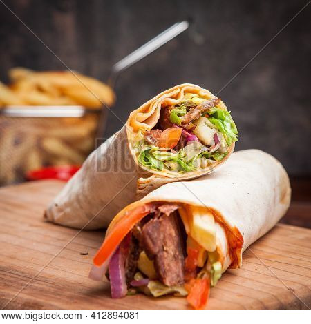 Side View Shawarma With Fried Potatoes In Board Cookware On Stone Background