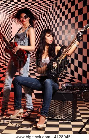Sitting and standing women play electric guitar and sing in studio with checkered background in red light.