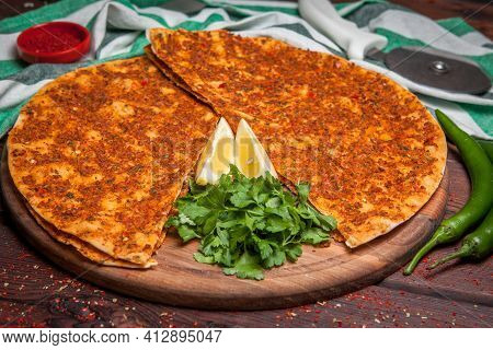Side View Lahmacun With Lemon And Parsley And Green Pepper In Board Cookware On Wooden Background
