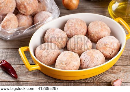 Side View Closeup On Raw Semi-finished Frozen Meatballs In A Baking Dish With Rice, Onion And Meat,