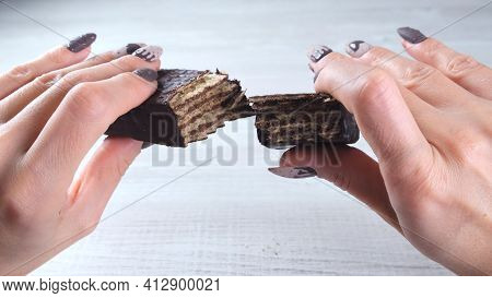 Female Hands With Beautiful Manicure Nails In The Form Of Chocolate Candies, Breaking An Unfolded Ba