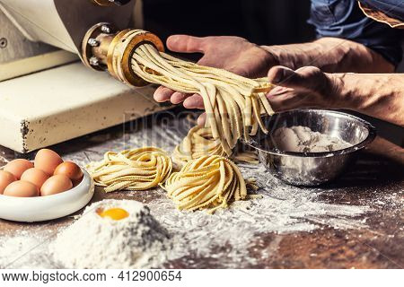Fresh Fettuccine Egg Dough Pasta Nests And Hands Of The Chef Holding Another Dose Of The Italian Spe
