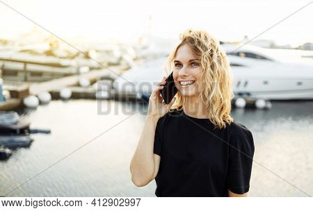Girl Talking On Phone While Standing On Pier