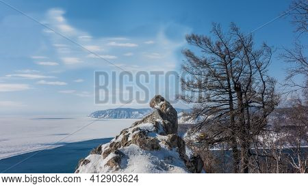A Picturesque Stone Of A Bizarre Shape Is Covered With Patches Of Snow. In The Distance You Can See