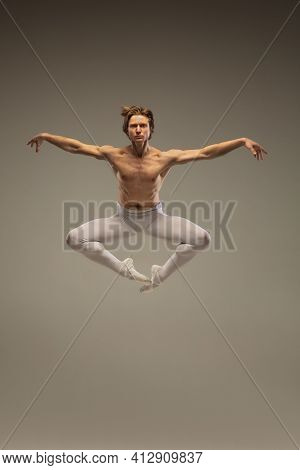 Powerful. Young And Graceful Ballet Dancer Isolated On Studio Background In Flight, Jump. Art, Motio