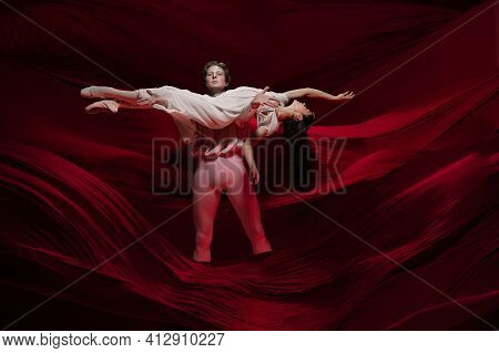 Feelings. Young And Graceful Ballet Dancers On Red Cloth Background In Classic Action. Art, Motion,