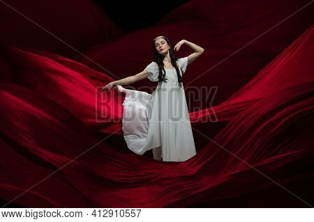 Flying. Young And Graceful Ballet Dancer On Flying Red Cloth Background In Classic Action. Art, Moti