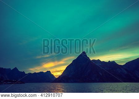 Fjord At Sunset, Rocky Beach In Evening. Silhouette Of Rocks Against Colorful Sunset Sky. Lofoten, R