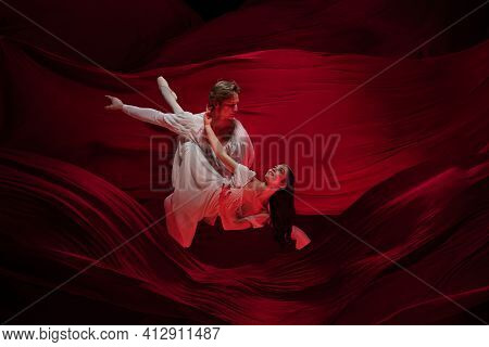 Fondly. Young And Graceful Ballet Dancers On Red Cloth Background In Classic Action. Art, Motion, Ac