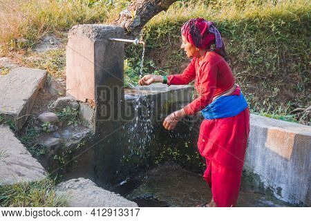 Nepali Village Woman Washing Face With Water At The Local Tap Placed In The Rural Village Of Nepal.
