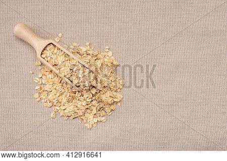 Oatmeal Cereal. Scoop And Pile Of Oatmeal With Its Plant. Dry Rolled Oatmeal. Wooden Scoop With Oat