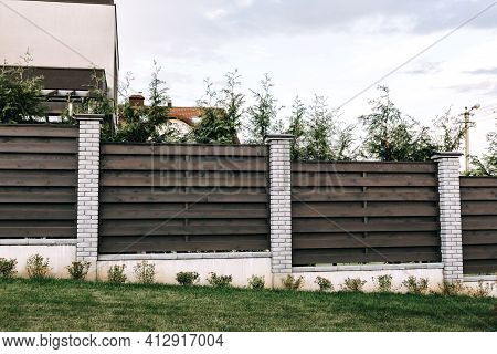 Horizontal Tiered Sections Of Brown Wooden Boards Fence And White Brick Pillars. Live Plantings. Gre